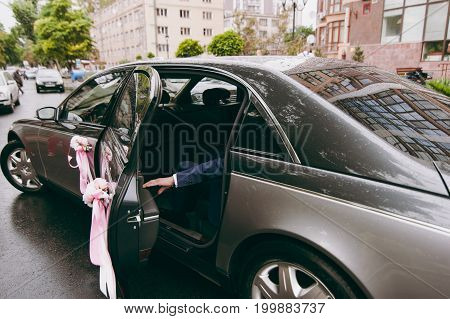 The portrait of the groom on a wedding day walk. The groom gets into the car.