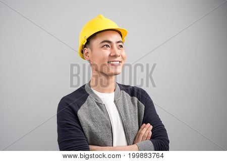 Portrait of smiling asian man wearing hardhat while standing arms crossed on gray background
