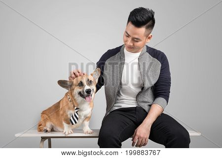 Young man sitting on chair with his own corgi