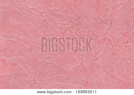 Light pink wavy background from a textile material. Fabric with fold texture closeup. Creased shiny rose cloth.