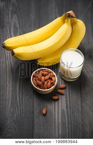 A Banch Of Bananas With Almonds And Milk On Wooden Background.