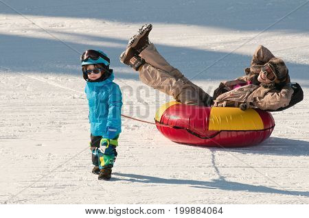 Snow Tubing Down The Hill, White Background. Color Image.