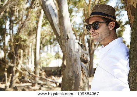 Guy leaning against tree in shades and hat