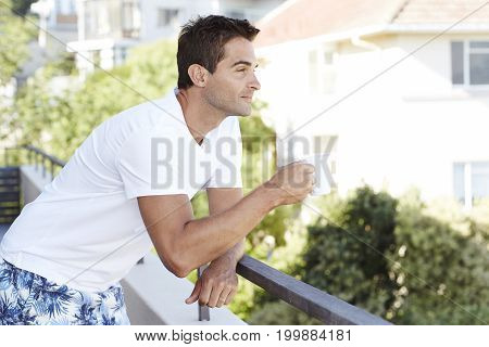 Dude in white t-shirt with coffee on balcony