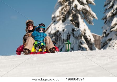 Mother An Son Sliding Down In Snow Tube, White Background. Color Image.