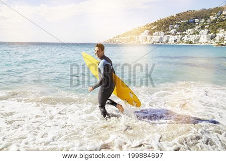 Surfer dude hitting the sea with surfboard smiling
