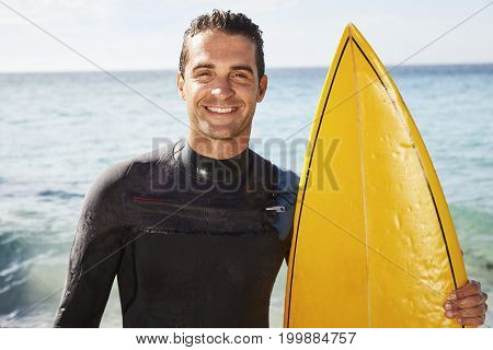 Smiling surfer dude in wetsuit holding surfboard