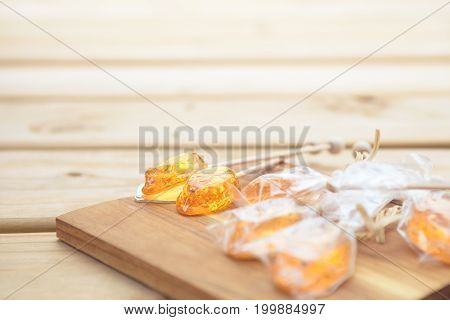 Honey caramel candy lollipop with sticks on wooden background. Products display, view.