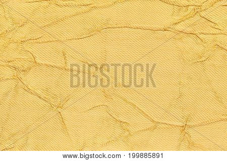 Light yellow wavy background from a textile material. Fabric with fold texture closeup. Creased shiny golden cloth.