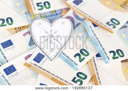 White and grey heart on euro banknotes bills. love and money
