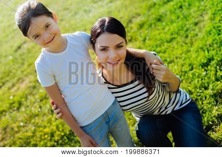Great time together. Charming little girl hugging her beloved mother squatting near her and both of them posing for the camera and smiling