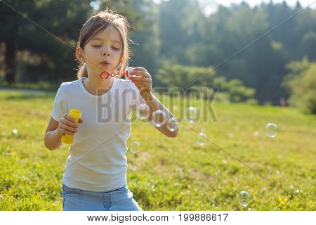 Favorite summer pastime. The close up of a charming little girl sitting on her knees in the forest meadow and blowing soap bubbles