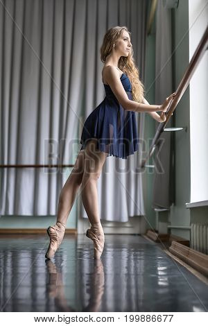 Pretty ballerina stands sideways on pointes in the ballet hall. She holds her hands on the ballet barre. Girl wears a blue dance wear with beige ballet shoes and looks into the window. Vertical.