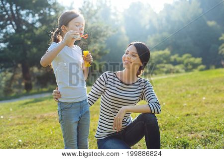 Mothers happiness. Loving young mother squatting near her beloved daughter, hugging her and watching her blow soap bubbles