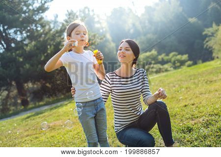 Happiest mother. Cheerful young mother hugging her beloved daughter and watching her play with soap bubbles