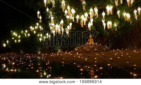 candles light at golden Buddha image with beautiful water reflection in Phan Tao Temple Chiangmai Thailand