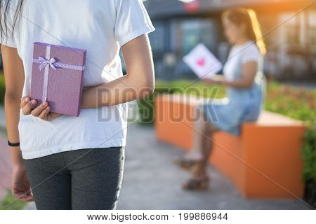 Mom reading leather postcard and children girl holding gift box surprise at park family lover or mother day happiness concept.