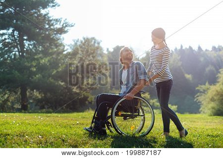Enjoying weekend. Slender caring woman carrying her young husband with disabilities in a wheelchair during a walk in the park while exchanging loving looks with him