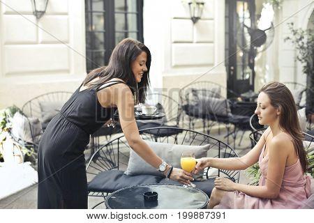 Waitress serving fresh orange juice in the garden of the hotel