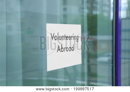 Sheet of paper with text VOLUNTEERING ABROAD on window glass