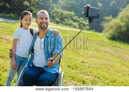 Collecting memories. Pleasant young man with disabilities hugging his adorable little daughter and taking a selfie with her, using a selfie stick