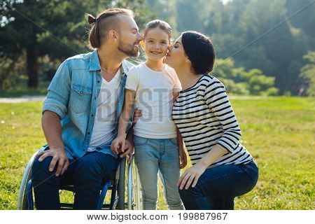 Beloved child. Gentle young mother and loving father with disabilities, sitting in a wheelchair, kissing their little daughter on both cheeks