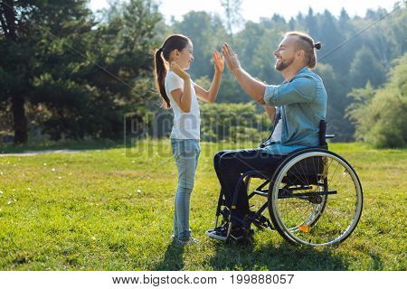 Great team. Charming young father with mobility impairment giving his adorable little daughter a high five while enjoying weekends outdoors
