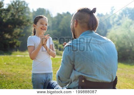 Enjoying game. Cheerful little girl playing pat-a-cake game with her father with mobility impairment during a walk in the park