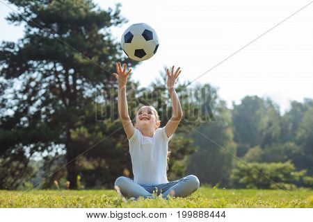 Entertaining herself. Pleasant little girl sitting on the grass in the middle of a sun-drenched meadow and throwing a ball in the air