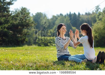 Mother-daughter bond. Pretty little girl sitting in her mothers lap in the sun-drenched meadow and giving her high ten while exchanging smiles with her