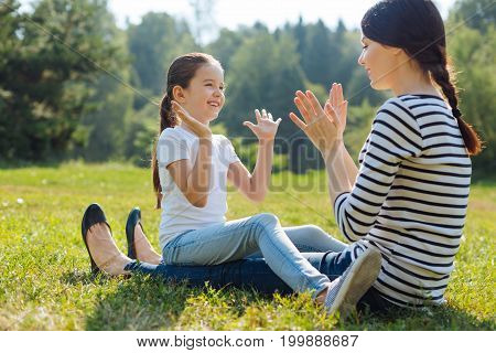 Full of affection. Adorable little girl sitting on her mothers lap and playing pat-a-cake game with her while smiling at her lovingly