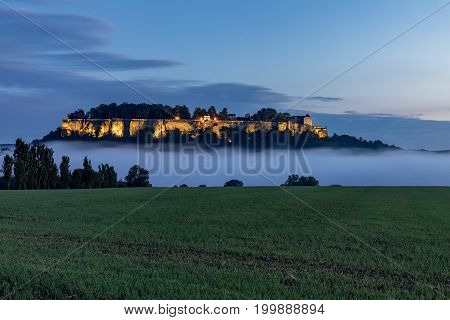 Germany. Saxon Switzerland. Enlightened Konigstein Fortress and mist in the Elbe Valley. Fortress wall of German castle Konigstein