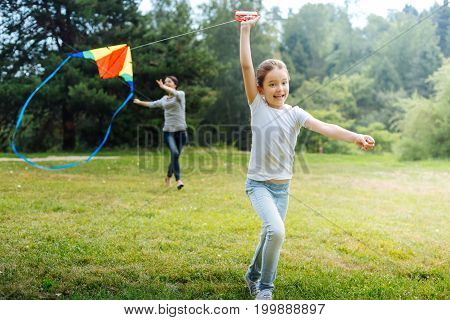 Favorite toy. Joyful little girl running across a meadow in the park and flying a kite together with her mother