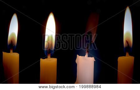 Extinguished candle among burning ones with smoke over dark background. Standing out from crowd concept. Exhausting or dying concept.