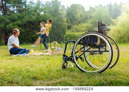 Enjoying life. The focus being on a wheelchair of a young man with mobility impairment watching his wife spin little daughter during a picnic in the park