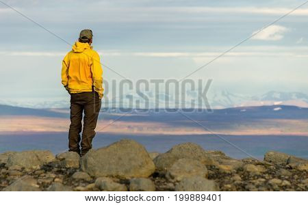 Relaxed man looking dreamfully towards snowy mountain range in icelandic highland. Iceland. Vintage retro style image.