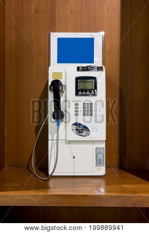 White vintage public pay phone on wooden booth