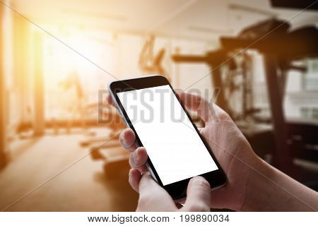 A Man Hand Holding Empty Screen Of Smart Phone Device In Gym.