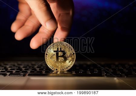 Hand holds a Single bitcoin coin or icon standing in sharp focus on a reflective surface