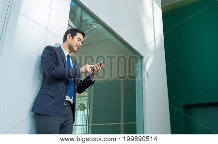 Businessman using mobile phone indise office buildingafter work lifestyle.