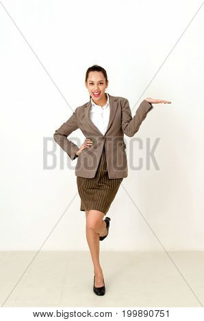 asian young business woman in suit standing on one leg and holding her hand palm up for ready to hold your product or object presentation on white background business lifestyle technology concept