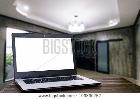 laptop computer with white blank screen for presentation on wooden desk with blurred view of modern living room interior at home copy space working at home online social media searching concept
