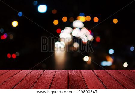 empty wooden floor or terrace with abstract night light bokeh blurred view of street traffic light in the city at night copy space for display of product or object presentation vintage color tone