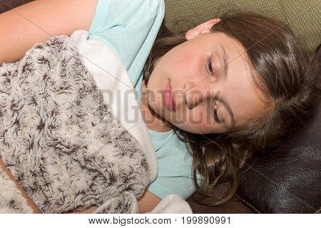 young sick teenager girl is lying on the sofa