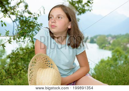 a pretty pre teen girl sitting in grass lake in background