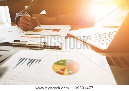 Man Hand With Pen Whit Business Report And Using Laptop Computer For Analyzing Financial Data