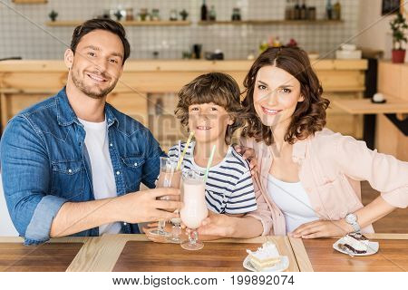 Happy Young Family Drinking Milkshakes In Cafe And Spending Time Together