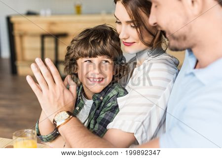 father giving high five to his son who sitting on mothers knees