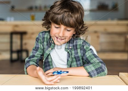 cute smiling boy with fidget spinner in hand