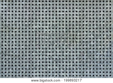 Metallic background with perforation of square holes.